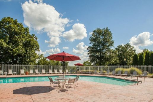 Fenced in large pool with patio tables with umbrellas, chairs, and sun chairs