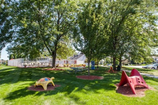 Children's play area with grass, trees and picnic table. Fenced in pool in background