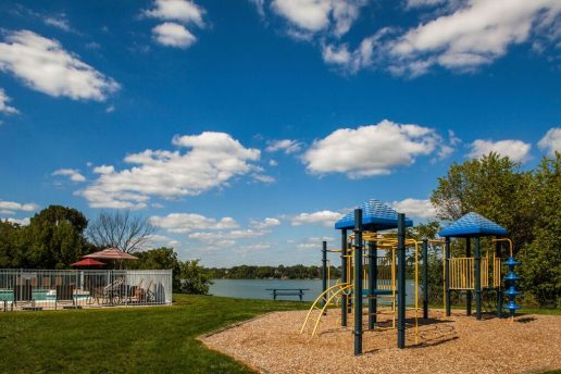 Children's play park with woodchips, picnic table, fenced in pool, and lake in background